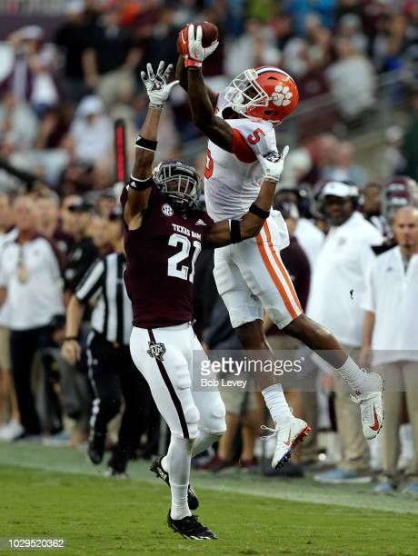 Tee Higgins of the Clemson Tigers leaps over Charles Oliver of the Texas AM Aggies to make a catch and runs for a 64 yard touchdown in the second...