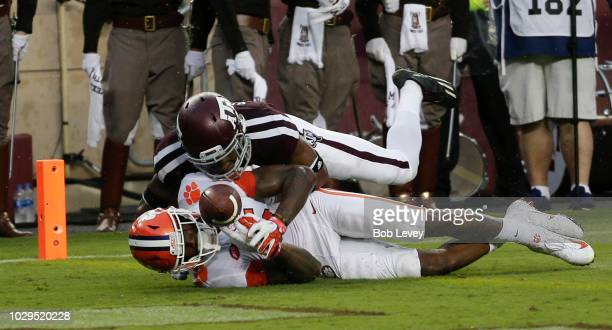 Tee Higgins of the Clemson Tigers scores on a 64 yard reception in the second quarter as Charles Oliver of the Texas AM Aggies is unable to stop him...