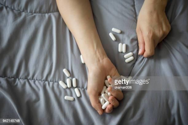 teeager holding medicine thinking suicide on bed - suicidio pastillas fotografías e imágenes de stock
