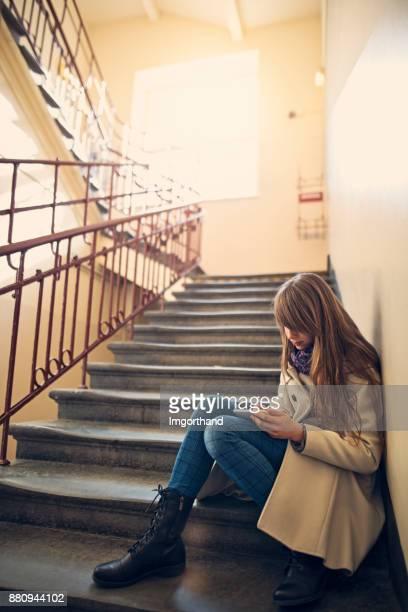 Teeange girl cheking social media on staircase