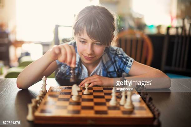 teeange girl playing game of chess - chess stock pictures, royalty-free photos & images