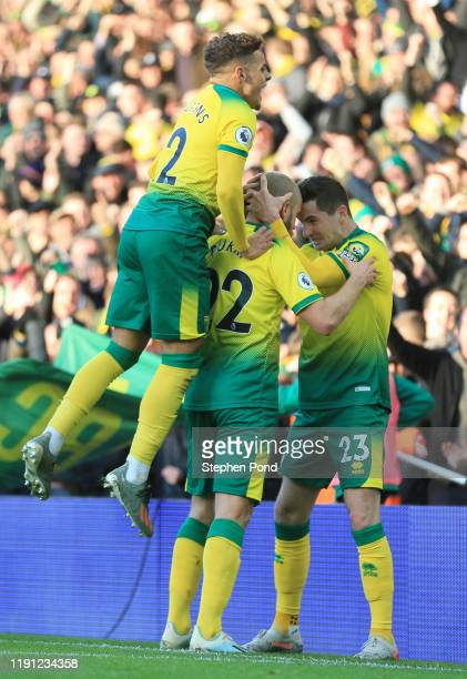 Teemu Pukki of Norwich City celebrates with Kenny McLean and Max Aarons after scoring his sides first goal during the Premier League match between...