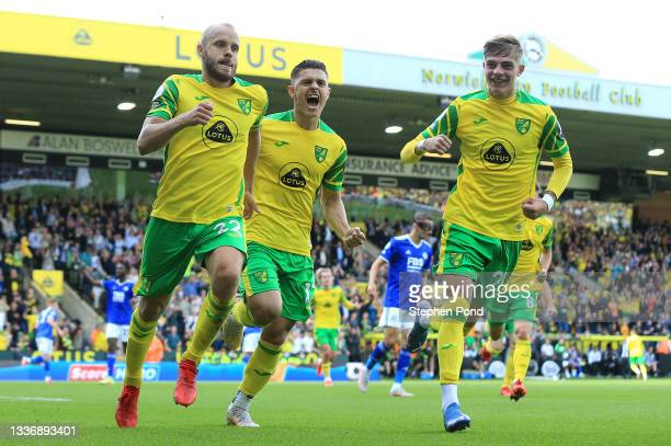 Teemu Pukki of Norwich City celebrates with teammates Milot Rashica and Brandon Williams after scoring his team's first goal during the Premier...