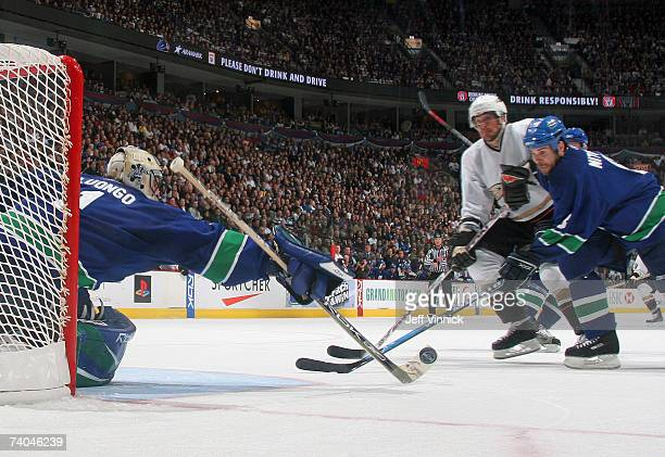 Teemu Selanne of the Anaheim Ducks and Willie Mitchell of the Vancouver Canucks look for a rebound as Roberto Luongo#1 of the Canucks makes a save...
