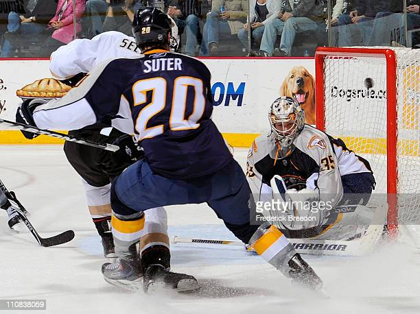 Teemu Selanne of the Anaheim Ducks fights through the defense of Ryan Suter of the Nashville Predators and scores a goal against goalie Pekka Rinne...