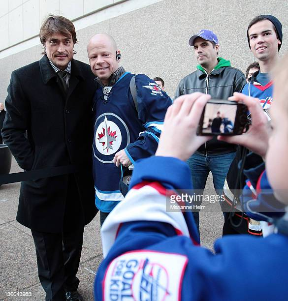 Teemu Selanne of the Anaheim Ducks has his photo taken with fan Gordon Hnytka as he leaves to take the bus to the MTS Centre outside the Fairmont...