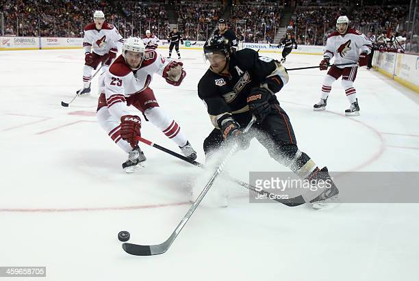 Teemu Selanne of the Anaheim Ducks is pursued by Oliver EkmanLarsson of the Phoenix Coyotes for the puck in the third period at Honda Center on...