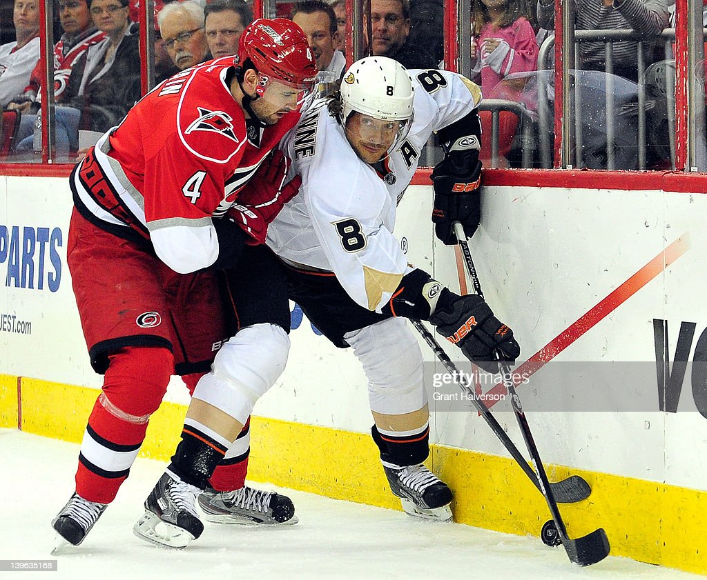 Teemu Selanne #8 of the Anaheim Ducks moves the puck against Jamie McBain #4 of the Carolina Hurricanes at the RBC Center on February 23, 2012 in Raleigh, North Carolina.