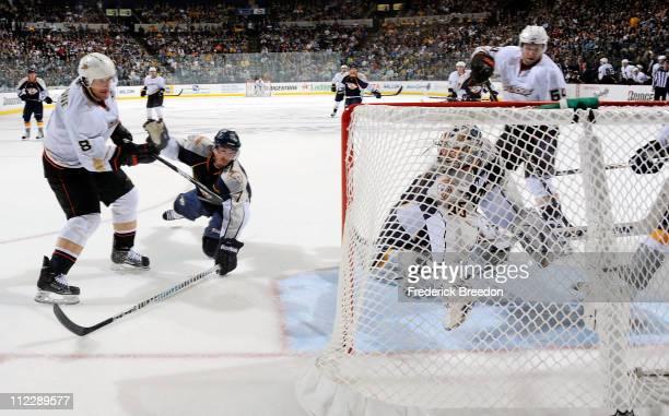 Teemu Selanne of the Anaheim Ducks shoots the puck past Jonathon Blum of the Nashville Predators and into the net behind Predators goalie Pekke Rinne...