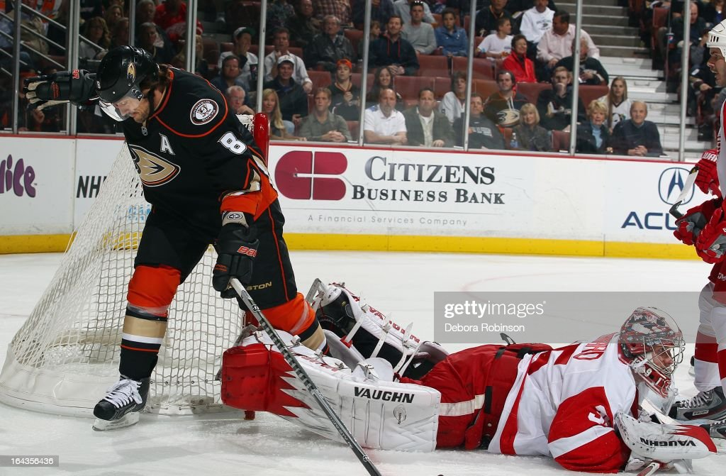 Teemu Selanne #8 of the Anaheim Ducks steps over Jimmy Howard #35 of the Detroit Red Wings after a shot at goal. March 22, 2013 at Honda Center in Anaheim, California.