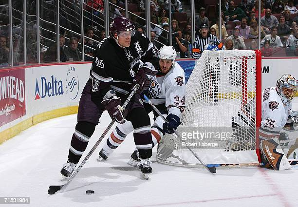 Teemu Selanne of the Mighty Ducks of Anaheim looks to center the puck as Fernando Pisani of the Edmonton Oilers tries to defend in game one of the...