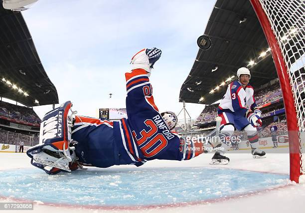 Teemu Selanne of the Winnipeg Jets alumni gets the puck past Bill Ranford of the Edmonton Oilers alumni to score a first period goal during the 2016...