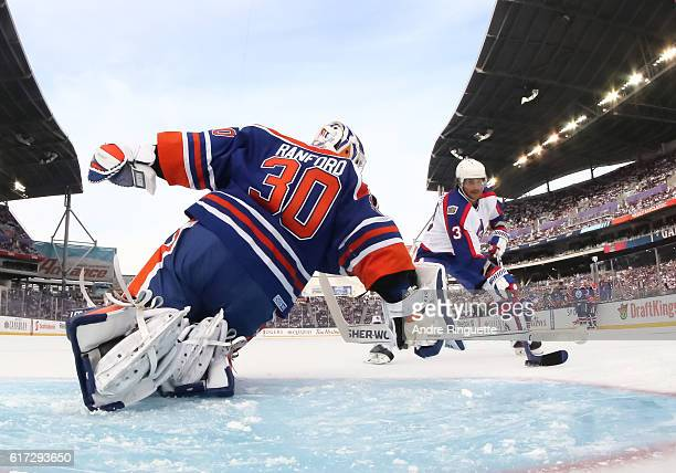 Teemu Selanne of the Winnipeg Jets alumni stickhandles the puck in on Bill Ranford of the Edmonton Oilers alumni to score a first period goal during...