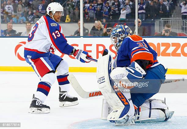 Teemu Selanne of the Winnipeg Jets alumni watches after taking a penaly shot on goaltender Curtis Joseph of the Edmonton Oilers alumni during the...
