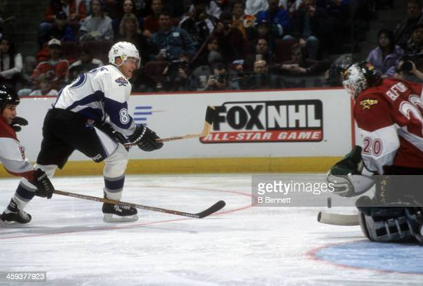 Teemu Selanne of the World and Mighty Ducks of Anaheim backhands a shot against goalie Ed Belfour of North America and the Dallas Stars during the...