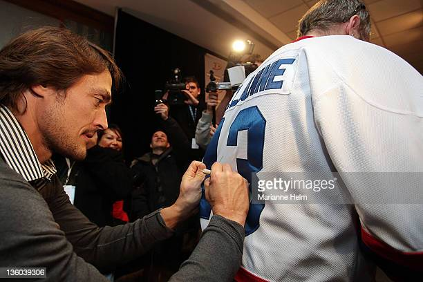 Teemu Selanne signs the jersey of fan Ryan Cheale after speaking with the media at the Fairmont Hotel on December 17 2011 in Winnipeg Manitoba Canada...