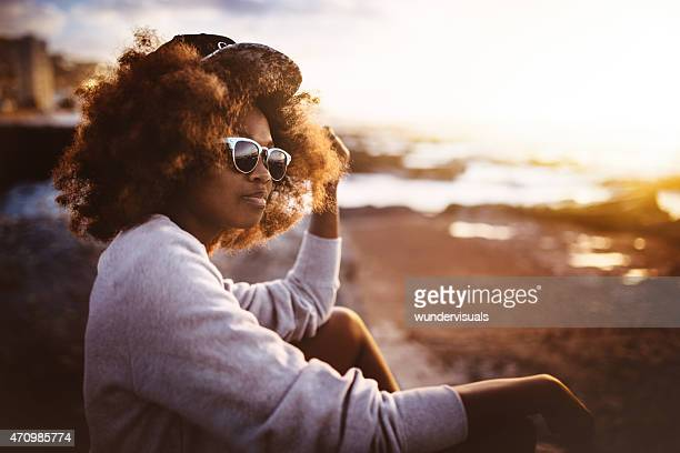 Teen Afro hipster girl sitting on beach looking on ocean