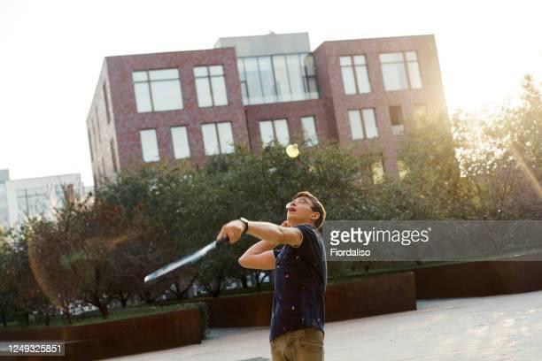 teen age boy  in glasses playing badminton in the city - linkshandig stockfoto's en -beelden