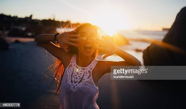 ティーンアジアの女の子が遊び心のあるサンセットオンザビーチ