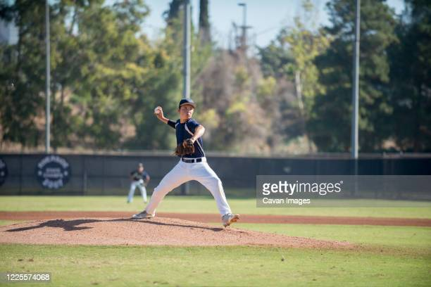 teen baseball player pitcher in blue uniform in full wind up on the mound - baseball pitcher stock pictures, royalty-free photos & images