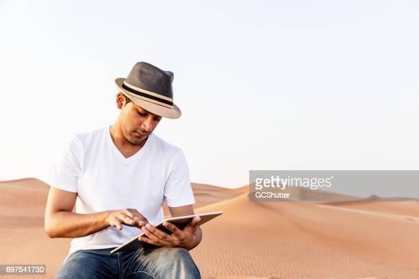 Tiener bloggen met behulp van zijn digitale tablet uit duinen van Arabië