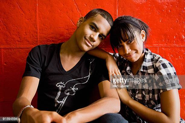 teen boy and girl in front of red wall, portrait - teenage couple stock pictures, royalty-free photos & images