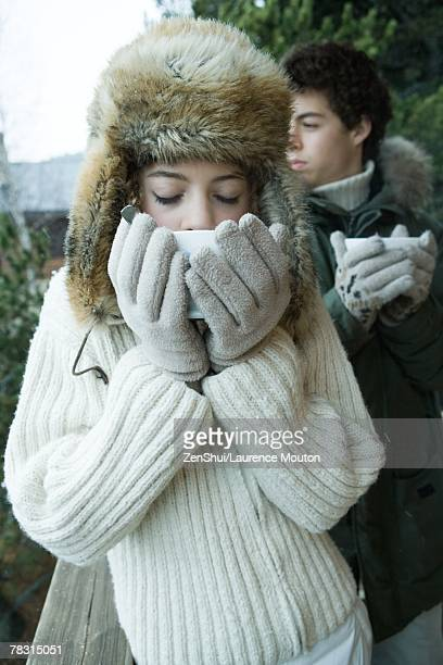 teen boy and girl in winter clothes drinking warm drinks - フード付きコート ストックフォトと画像