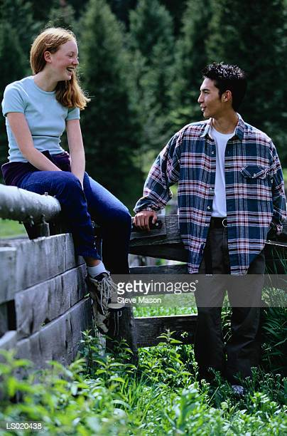 Teen Boy and Girl Talking by a Fence