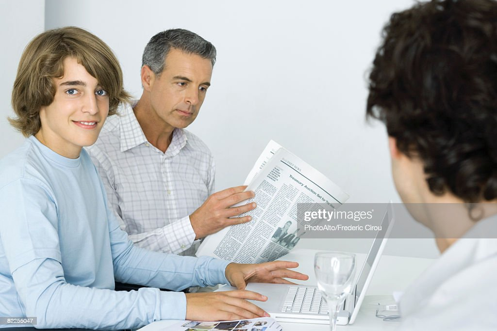 Teen boy at table with father, using laptop computer, man reading newspaper : Stock Photo