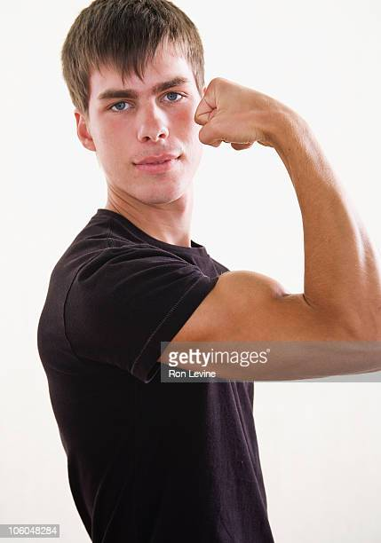 Teen boy flexing his bicep, portrait