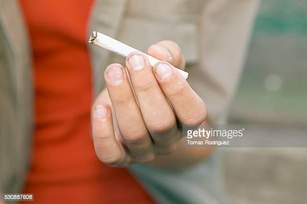 Teen boy holding cigarette