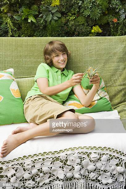 teen boy holding plant - teen boy barefoot stock photos and pictures