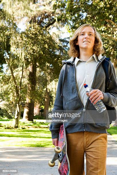 Teen boy holding skateboard and water bottle