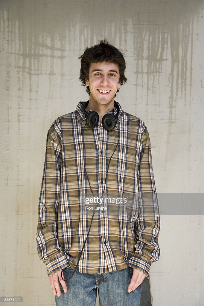 Teen boy in plaid shirt and headphones, portrait : Stock Photo