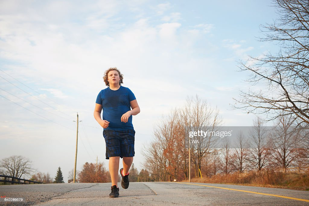 Teen boy jogging on country road : Stock Photo