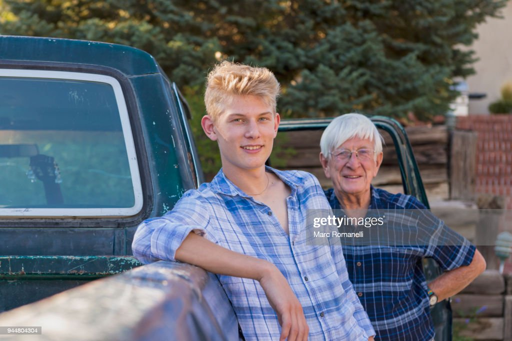 teen boy leaning on pick up truck with grandfather in background : Stock Photo