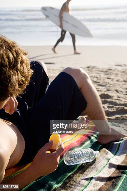 Teen boy on beach holding orange