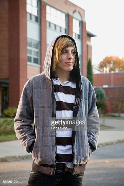 Teen boy outside high school looking away