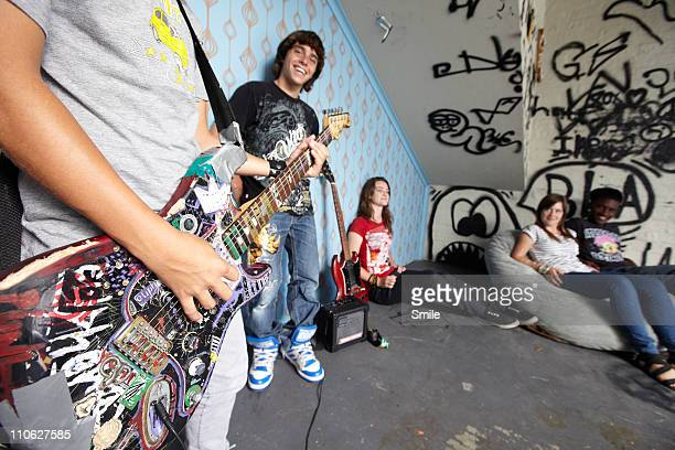 Teen boy playing electric guitar for friends