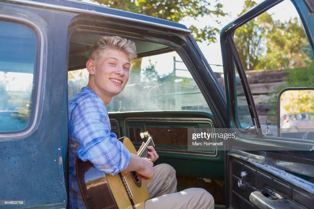 teen boy playing guitar in pick up truck : Stock Photo