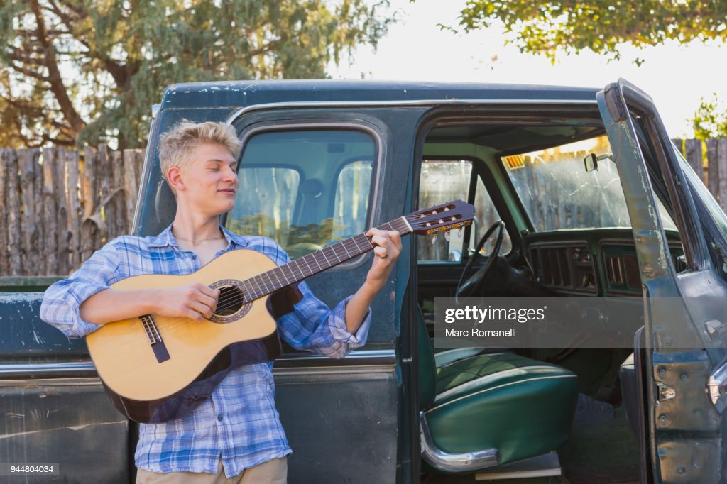 teen boy playing guitar,  leaning on  pick up truck : Stock Photo