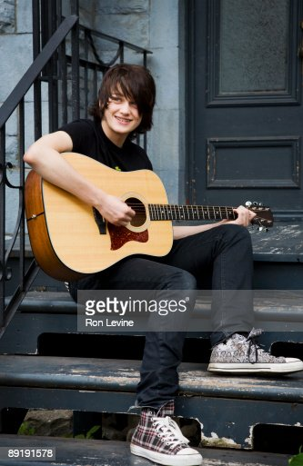 Portrait Of Teenage Boy Sitting On Terrace Playing Acoustic Guitar