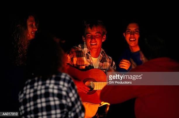 teen boy playing guitar with camping friends - seulement des adolescents ou adolescentes photos et images de collection