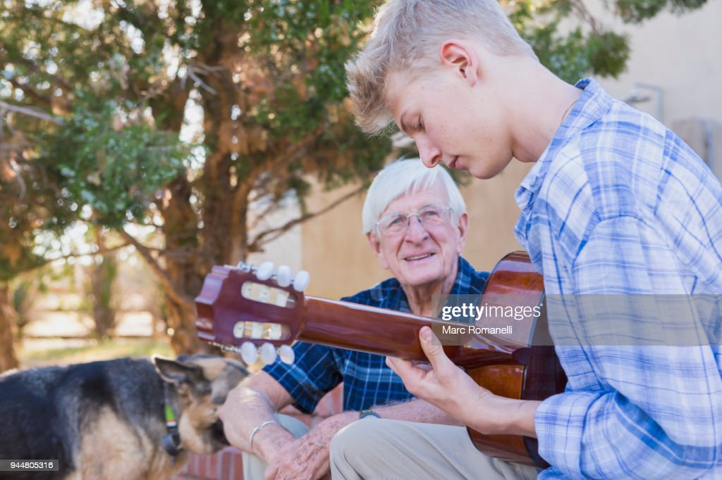 teen boy playing guitar with with grandfather listening : Stock Photo