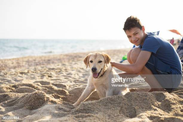 Teen boy playing with dog at the beach
