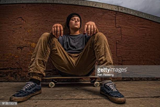 Teen boy portrait sitting on skateboard