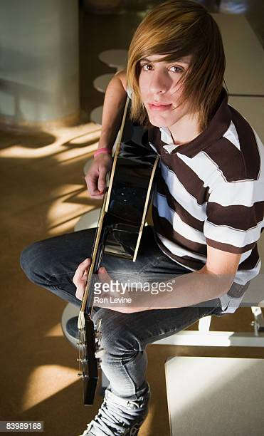 teen boy practicing guitar in school cafeteria - emo stock photos and pictures
