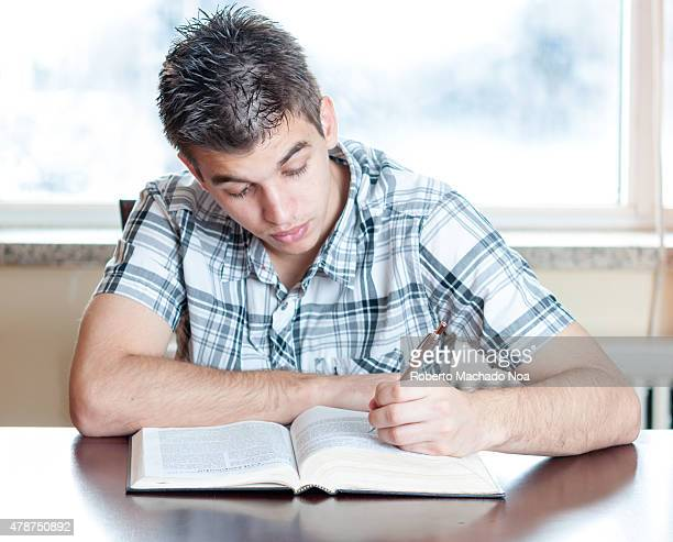 Teen boy prepares for school by studying his textbook and taking notes