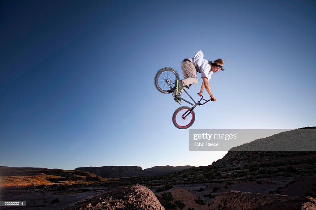 A teen boy riding and jumping his BMX bicycle over dirt hills : Stock Photo