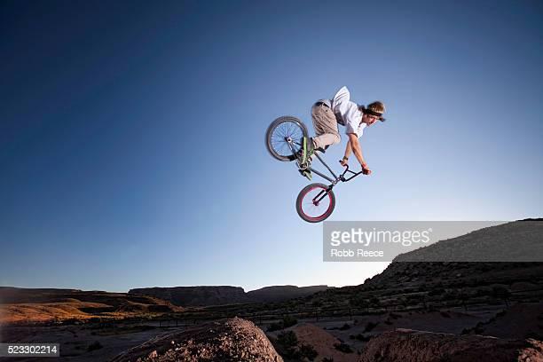 a teen boy riding and jumping his bmx bicycle over dirt hills - robb reece fotografías e imágenes de stock
